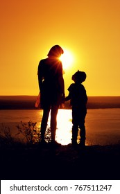 Silhouettes of mom and son holding hands and admiring the beautiful view of the sea on sunny evening at sunset time