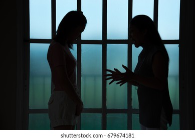 Silhouettes of mother arguing with her teenage daughter, family problem concept,copy space.