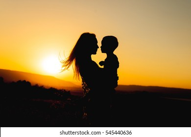 Silhouettes of mother and child in her arms on the background of sunset sky