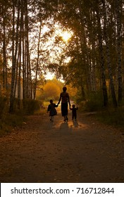 Silhouettes of mother with children on a warm sunny day in the autumn city park.