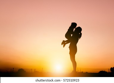 Silhouettes of mother and daughter playing at sunset evening sky background.