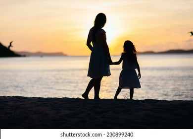Silhouettes of mother and daughter walking along tropical beach during sunset
