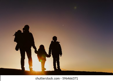 Silhouettes of mother with two kids hiking at sunset