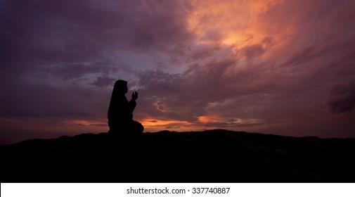 silhouettes of  muslim women praying during sunset