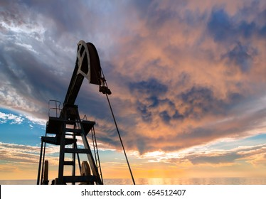 Silhouettes of oil pumps (pumpjack) at stormy sky