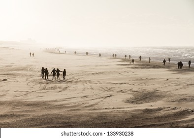 Silhouettes on the beach on a sunny day with storm winds in the Netherlands