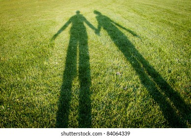 Silhouettes over grass - illustrates the concept of a couple