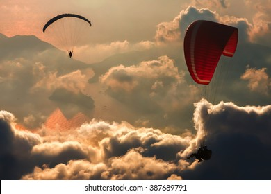 Silhouettes of para glider over the clouds