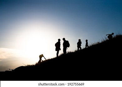 Silhouettes of parents with children rising uphill