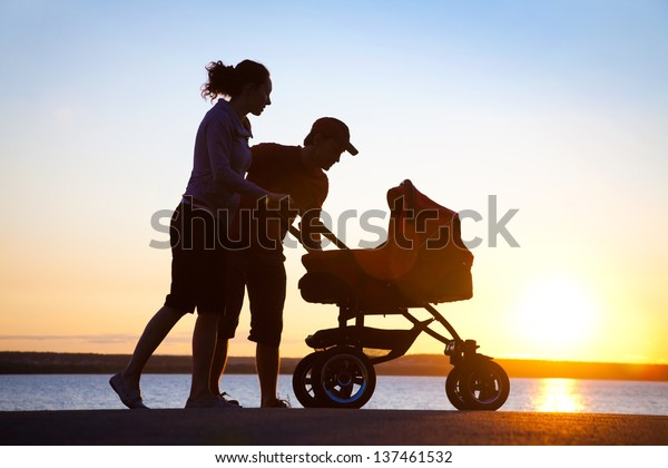 Silhouettes of parents loving  their child in a stroller