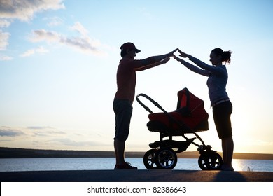 Silhouettes of parents protect their child in a stroller
