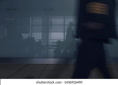 Silhouettes of passengers at airport gate awaiting boarding