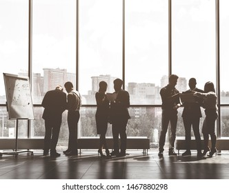 Silhouettes of people against the window. A team of young businessmen working and communicating together in an office. Corporate businessteam and manager in a meeting.