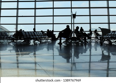 Silhouettes of people in airport. People waiting airplane for departure
