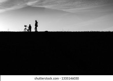 silhouettes of people and a bicycle