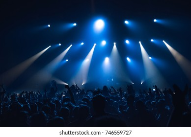 Silhouettes of people in a bright in the pop rock concert in front of the stage. Hands with gesture Horns. That rocks. Party in a club. Sold out.