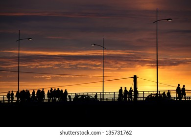 silhouettes of people and cars crossing the bridge at sunset, urban scene, vibrant colors