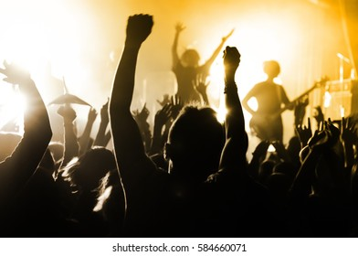 silhouettes of people at a concert in front of the scene in bright light