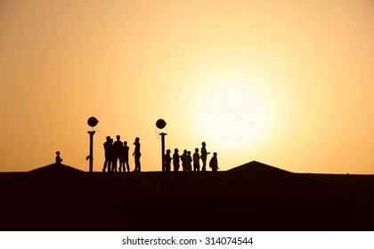 Silhouettes of people in the desert at sunset, hiking, walking, summer heat