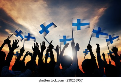 Silhouettes of People Holding the Flag of Finland