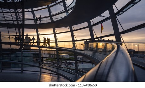 Silhouettes people inside glass dome on Reichstag building with sunset sky, Berlin, Germany, April 29th 2018