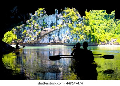 The silhouettes of people kayaking inside of a cave in Lan Ha Bay, close to Halong Bay, Vietnam