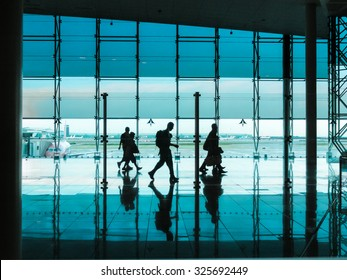Silhouettes of people with luggage walking at airport.