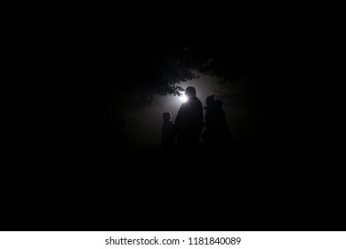 Silhouettes of people at night in the forest