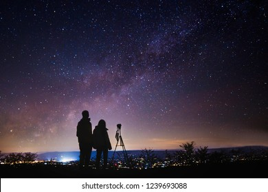 Silhouettes of people observing stars during night and taking photo of starry sky. Astronomy and Astrophotography concept.