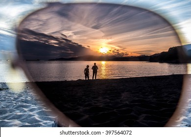 Silhouettes of People on the Beach in English Bay, Vancouver Through Sunglasses