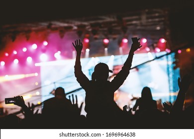 Silhouettes of people with raised hands at a concert. Stage light