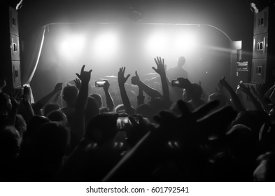 silhouettes of people at a rock festival concert in front of the scene in bright light
