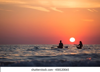Silhouettes of people romancing in the ocean at sunset.