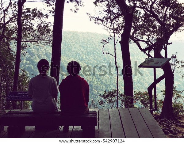 Silhouettes People sit in a mountain forest.