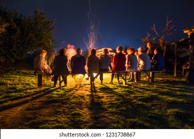 Silhouettes of people sitting around a campfire at night.  Tourists relax by the fire. long exposure