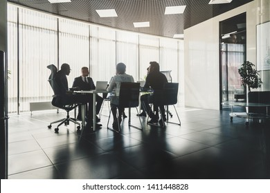Silhouettes of people sitting at the table. A team of young businessmen working and communicating together in an office. Corporate businessteam and manager in a meeting.