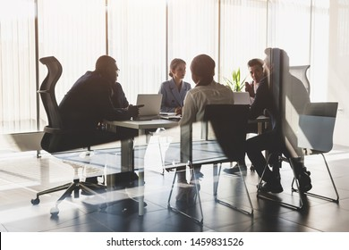 Silhouetten von Leuten, die am Tisch sitzen. Ein Team junger Geschäftsleute, die in einem Büro zusammenarbeiten und kommunizieren. Unternehmensführung und Geschäftsführer in einem Meeting