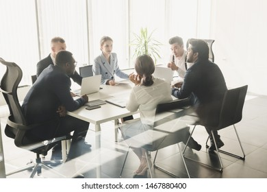 Silhouettes of people sitting at the table. A team of young businessmen working and communicating together in an office. Corporate businessteam and manager in a meeting