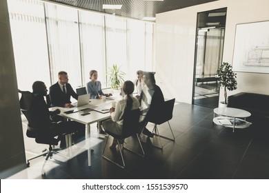 Silhouetten von Leuten, die am Tisch sitzen.Ein Team junger Geschäftsleute, die in einem Büro zusammenarbeiten und kommunizieren. Unternehmensführung und Geschäftsführer in einem Meeting