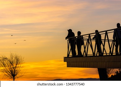 Silhouettes of people at sunset and clouds in the red sky.