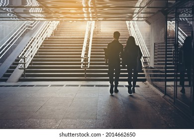 Silhouettes of people. People in underground crossing. View from the back. Couple of young people on the crosswalk. The couple is holding hands and walking on the city. Unknown people. Street photo