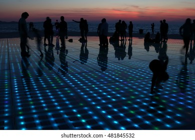 silhouettes of people in various activities at the seawall of Zadar, upon sunset, Croatia