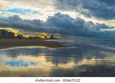Silhouettes of people walking along the beach of Ostend City during storm weather with a dramatic sky with a reflection at sunset, Belgium.