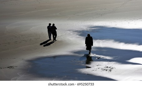 Silhouettes of people walking on the beach in winter,peace, calm, serenity, harmony, fullness, well-being, nature, natural, contemplate, meditate, breathe, grow, happiness, tranquility, plenitude,
