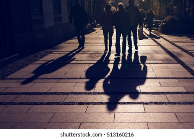 Silhouettes of people walking on city street and casting shadows on pavement, general public concept for any community related theme