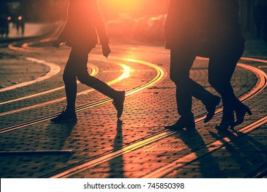 Silhouettes of people walking on city street and casting shadows on pavement with railway tracks in Bordeaux, grain texture apply