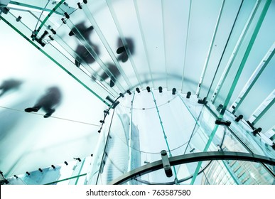 Silhouettes of people walking on a glass spiral staircase