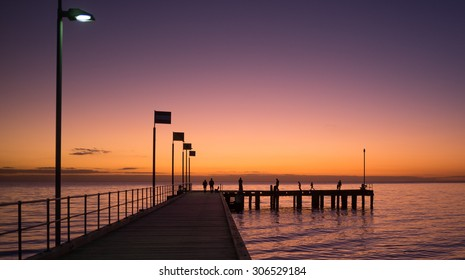 Silhouettes of people walking on a pier at sunset, Victoria, Australia