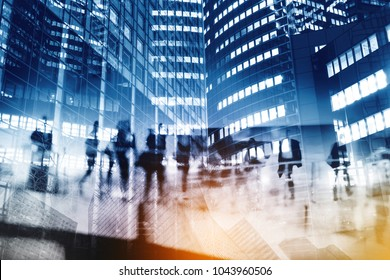 Silhouettes of people walking in the street near skyscrapers and modern office buildings in Paris business district. Multiple exposure blurred image. Economy, finances, business concept illustration.