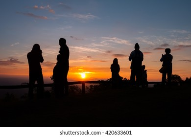 Silhouettes of peoples take photos  on top of mountain with sunrise at samer dao mountain, Nan province, Thailand